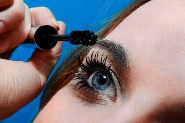 Applying castor oil to eyelashes with mascara wand